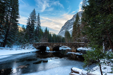 Wall Mural - Snowy winter scene on a road with Half Dome in the background in Yosemite National Park