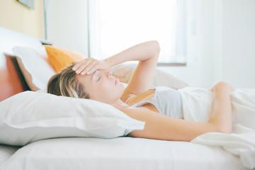 Donna a letto con mal di testa o stressata