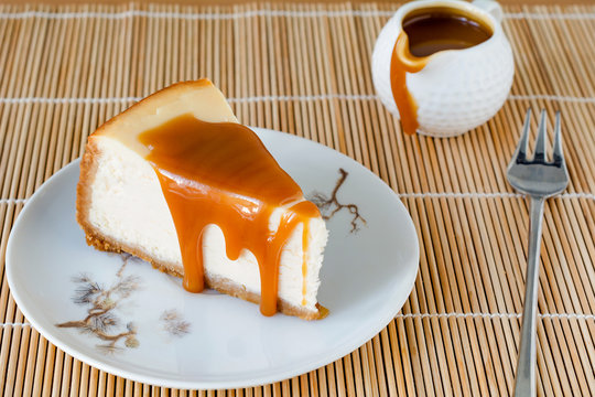 Slice of New York cheesecake with caramel sauce on a plate
