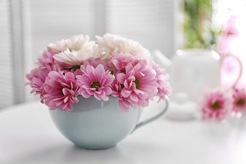 Chrysanthemum bouquet in cup on table