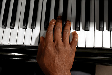 Afro American man hand playing piano