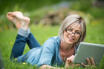 a woman of 50 years who is using her tablet in grass