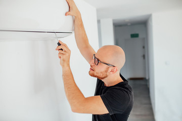 Man is repairing an air condition. Home background