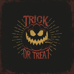 "Vintage lettering with a Halloween pumpkin and the words ""trick or treat"" and sunburst on a dark background. Vector illustration. Grunge texture on separate layers."