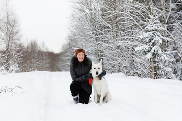 Woman with white swiss shepherd dog in winter forest