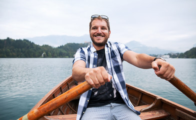 Tourist traveling by traditional wooden boat on the Lake Bled, Slovenia