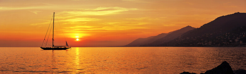 Poster de jardin Mer coucher du soleil Panoramic view of Sailing at sunset with mountains