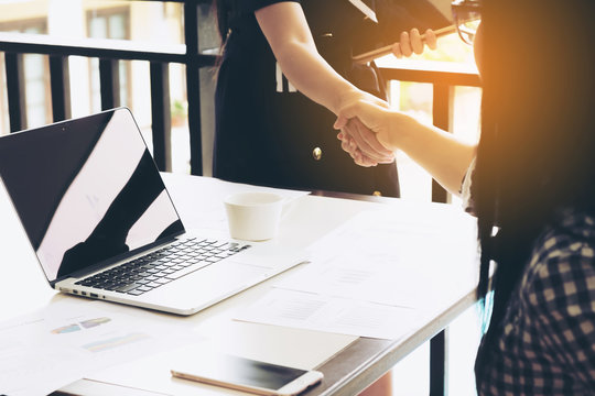 Two Businesswoman Having Handshake In Office