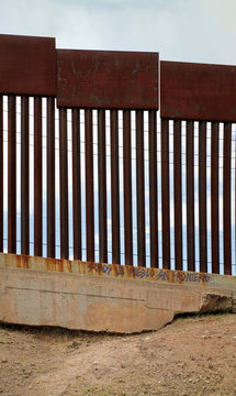 """US-Mexican border as seen from Nogales, Mexico. The Spanish graffiti translates: """"We are a people without borders""""."""