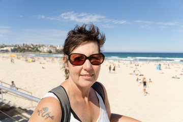A middle aged woman in sunglasses enjoying visiting Bondi Beach in Sydney, Australia, with short hair, sunglasses, and a tattoo on her shouler.