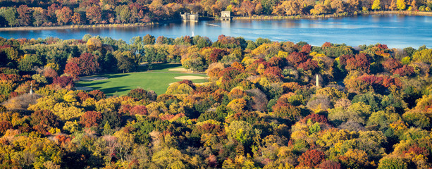 Panoramic aerial view of Central Park, Jacqueline Kennedy Onassis Reservoir and the Great Lawn with colorful Fall foliage. New York City