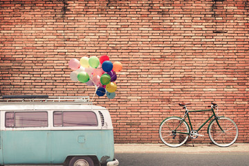 Vintage style photo card - classic car (vintage van) in city with colorful balloon on roof parked on road in urban. concept of love in summer and wedding, honeymoon.