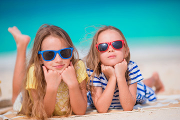 Adorable little girls during summer vacation. Kids on the white beach