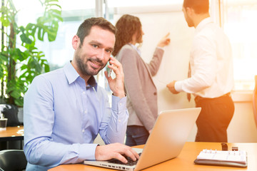 Young attractive businessman working at the office with associat