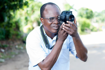 young man taking pictures with a digital camera in campaign