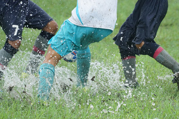 Young girls playing soccer in the rain on a wet grassy field