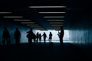 Silhouette of musician with saxophone in underpass