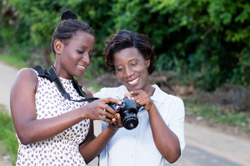Young photographer showing  her  girlfriend the beautiful pictures she took her