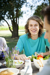 Young man enjoying meal with friends outdoors
