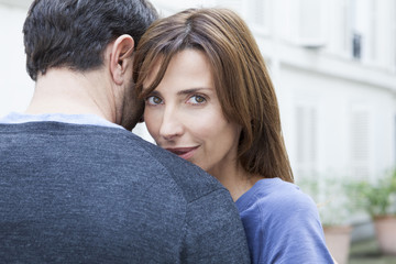 Couple embracing, woman looking at camera