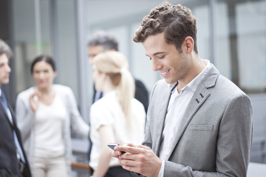 Businessman using cell phone while on the move