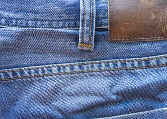 синяя джинсовая ткань. линялые синие джинсы. старые джинсы кожаная бирка