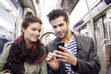 Young couple using smartphone in train