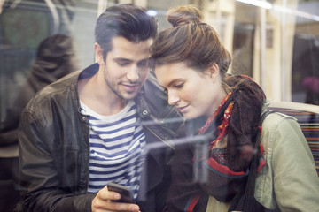 Couple on subway looking at smartphone together