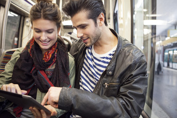 Happy young couple using digital tablet in train