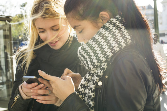 Young women together looking at their individual smartphones