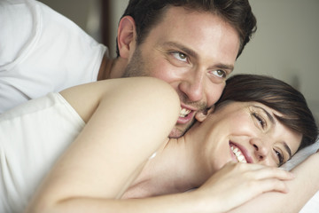 Couple playfully cuddling in bed
