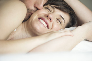Close up of man kissing woman on bed