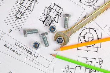 Wrench, pencil, bolts and nuts on background of engineering drawings. Science, mechanics and mechanical engineering