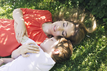 Mother and son napping on grass