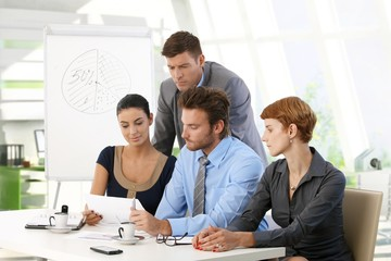 Business team reading papers at office meeting