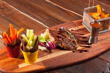 pork steak with French fries on a wooden cutting board