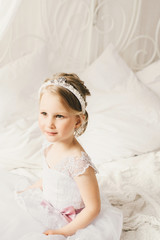 Little bride sitting on the bed in a beautiful dress