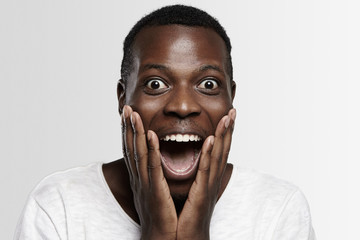 Shocked African student or employee looking at camera in full disbelief, hands on cheeks, mouth wide open, surprised with some unexpected news or big sale prices. Human face expressions and emotions