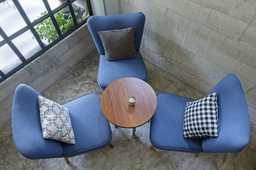 set of chairs with pillows and wooden table indoor near a window