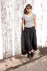 Hipster woman wearing sunglasses dressed in urban minimal style