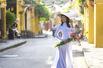 Beautiful woman with Vietnam culture traditional dress, Ao dai is famous traditional costume , vintage style, Hoi an Vietnam, holding the flowers