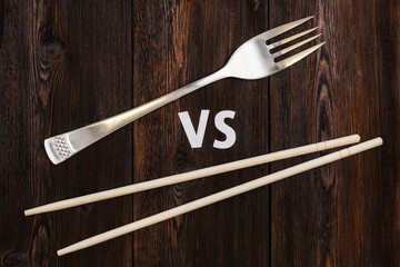 Wooden pairs of chopsticks vs fork. Abstract conceptual image