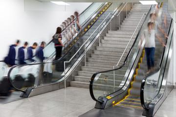 people on moving escalator motion blur