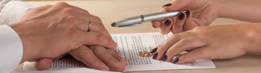 Wife and husband signing divorce documents or premarital agreement