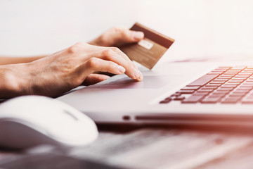 Hands holding credit card and using laptop. Online shopping e-commerce concept