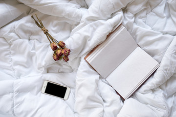 Dry roses, smartphone and vintage notebook on bed