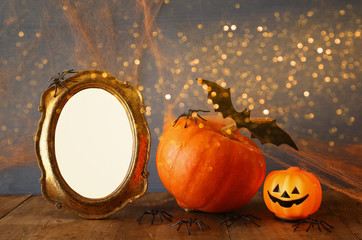 Halloween concept. Cute pumpkin next to blank photo frame