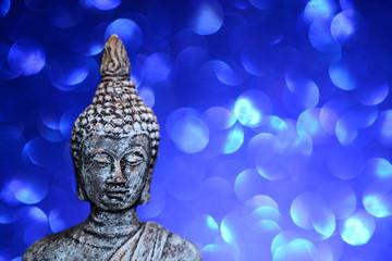 Zen Buddha statue on a bright shiny glitter background with bokeh