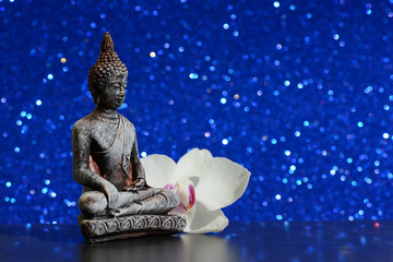 Buddha statue and a orchid flower on a bright shiny glitter background with bokeh