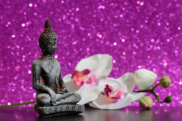 Buddha statue and a orchid flower on a bright pink shiny glitter background with bokeh